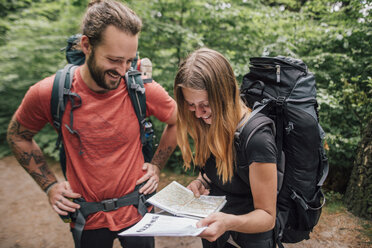 Happy young couple on a hiking trip reading map - GUSF00725