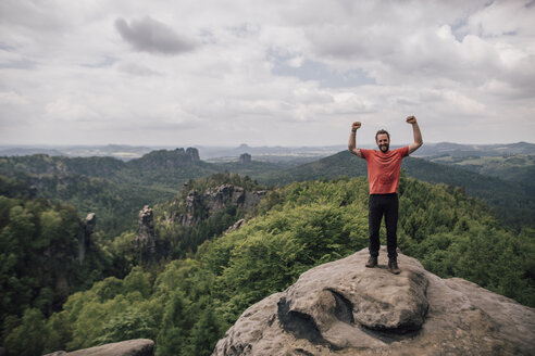 Germany, Saxony, Elbe Sandstone Mountains, man on a hiking trip standing on rock cheering - GUSF00737