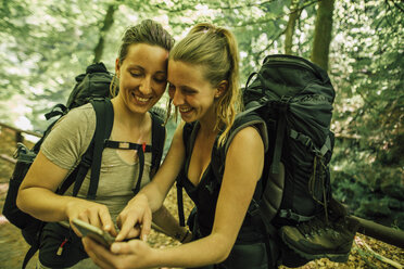 Two happy young women on a hiking trip using cell phone - GUSF00743