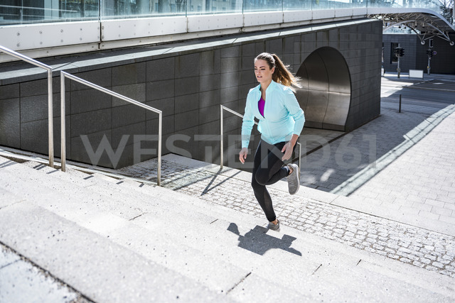 Young woman running on stairs in the city - DIGF04034