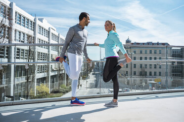 Couple doing stretching exercise on bridge in the city - DIGF04043