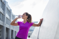 Young woman having a break from exercising drinking from bottle - DIGF04052