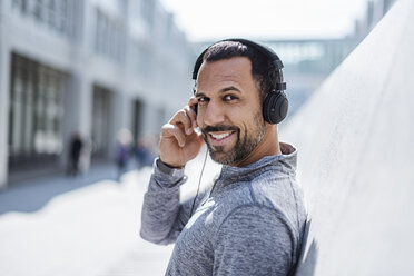 Portrait of smiling man having a break from exercising wearing headphones - DIGF04055
