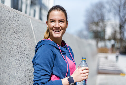 Smiling young woman having a break from exercising - DIGF04058