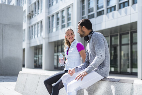 Active couple with water bottle having a break in the city - DIGF04061