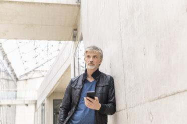 Mature man using smartphone - FMKF05032