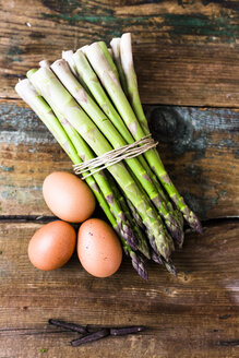 Green asparagus and brown eggs on wood - GIOF03923