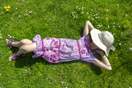 Girl lying on meadow in garden - SARF03694
