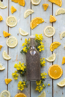 Chia drink in bottle and slice of orange and lemon on wood - SKCF00446