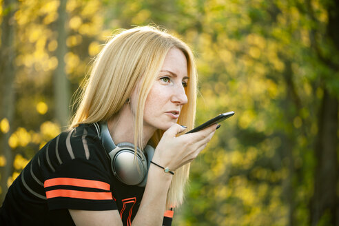 Portrait of blond woman with headphones using smartphone - NAF00090