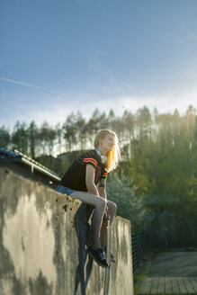 Smiling blond woman with longboard sitting on wall looking at distance - NAF00093