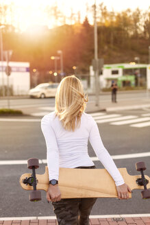 Back view of blond woman with longboard - NAF00096