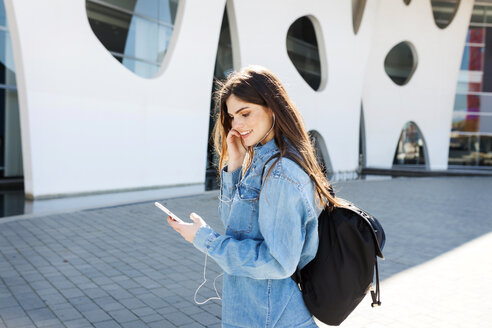 Spain, Barcelona, smiling young woman with backpack listening music with cell phone and earphones - VABF01554