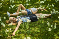 Two friends relaxing on flower meadow - BEF00007