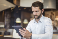 Young businessman using tablet in a cafe - DIGF04081