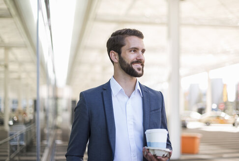 Smiling young businessman holding tray with takeaway coffee - DIGF04084