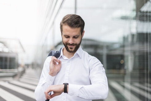 Smiling young businessman checking the time - DIGF04102