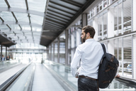 Young businessman with backpack on moving walkway - DIGF04105