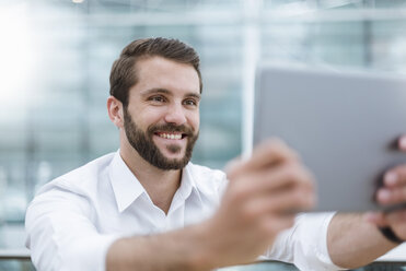 Smiling young man taking a selfie with tablet - DIGF04117