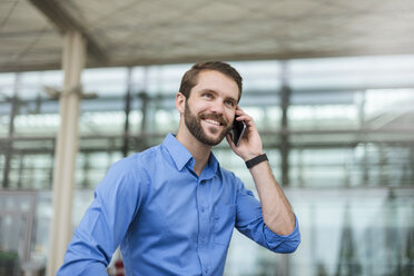 Smiling young businessman on cell phone outdoors - DIGF04120
