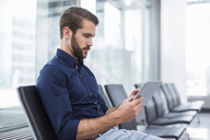 Young businessman sitting in waiting area using tablet - DIGF04126