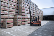 Worker on forklift and stacks of crates on factory yard - ZEF15400