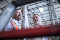 Businessman and man in reflective vest talking in industrial hall - ZEF15409