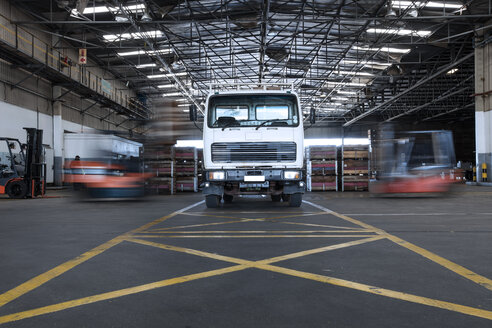 Parked truck in warehouse and moving forklifts - ZEF15421