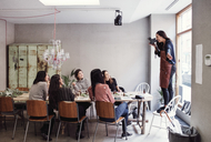 Cheerful woman standing on chair photographing female colleagues sitting at table in workshop - MASF07208