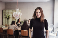 Portrait of confident female brunette owner standing against colleagues in workshop - MASF07220
