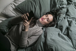 High angle view of woman using smart phone while lying on bed - MASF07265