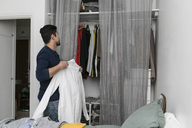 Side view of young man arranging clothes in closet at bedroom - MASF07268
