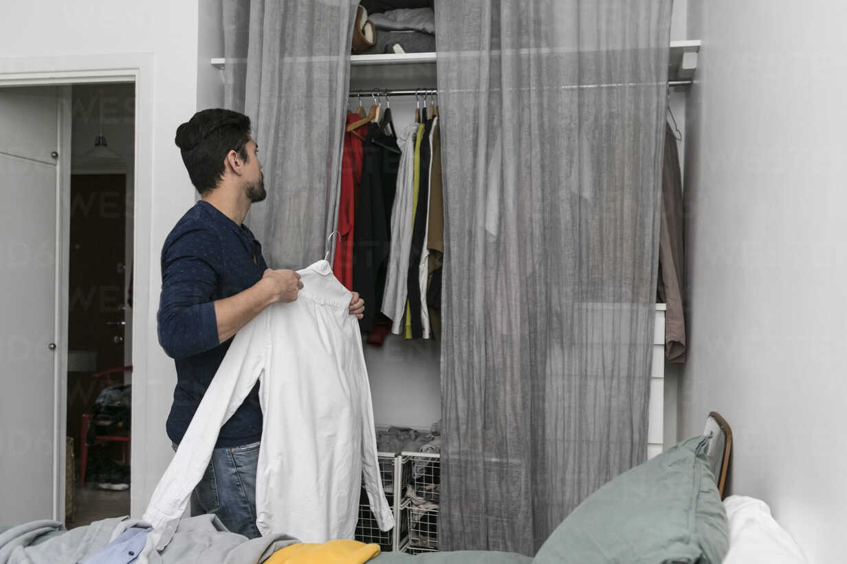Side View Of Young Man Arranging Clothes In Closet At Bedroom Stockphoto