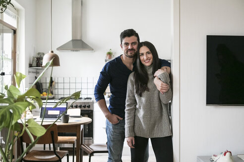 Portrait of smiling couple standing by wall at home - MASF07280