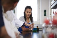 Female student looking at teacher holding beaker with solution in chemistry laboratory - MASF07310
