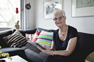Portrait of confident senior woman sitting with digital tablet on sofa in living room at home - MASF07373