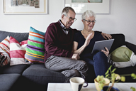 Smiling senior couple sitting on sofa sharing digital tablet in living room at home - MASF07403
