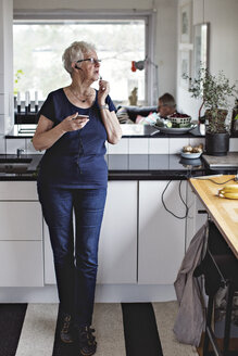 Full length of senior woman standing with smart phone in kitchen at home - MASF07412
