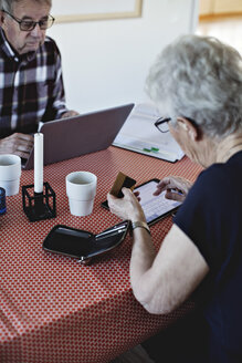Senior woman holding credit card while using digital tablet at dining table - MASF07433