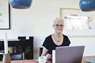 Portrait of smiling retired senior woman sitting with laptop at dining table - MASF07451