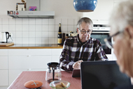 Senior couple using technologies sitting at dining table - MASF07454