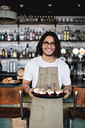 Portrait of smiling waiter holding dessert in tray while standing against counter in restaurant - MASF07490