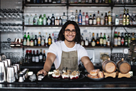 Portrait of smiling owner with food standing at counter in restaurant - MASF07493