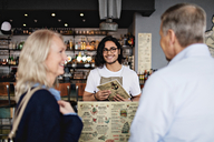 Smiling owner looking at mature couple with menu in restaurant - MASF07496