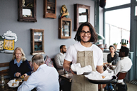 Portrait of smiling young waiter serving food while standing against customers at restaurant - MASF07529