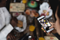 Cropped image of woman photographing food on dining table at restaurant - MASF07532