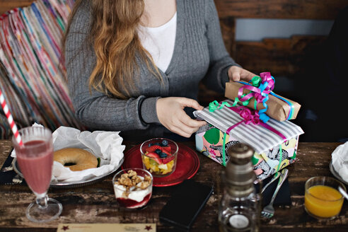 Midsection of young woman holding gifts amidst food and drinks at dining table in restaurant - MASF07535