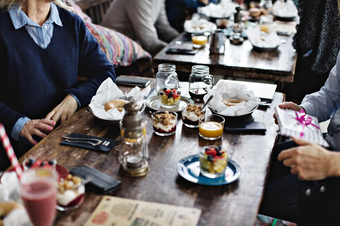 Midsection of couple eating brunch at dining table in restaurant - MASF07538