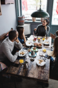 High angle view of friends talking while having food at dining table - MASF07544