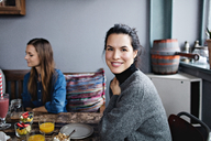 Portrait of smiling woman having brunch with friend at table - MASF07547
